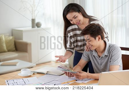 Portrait of young Asian couple gathered together at cozy living room and choosing colors while planning new house design
