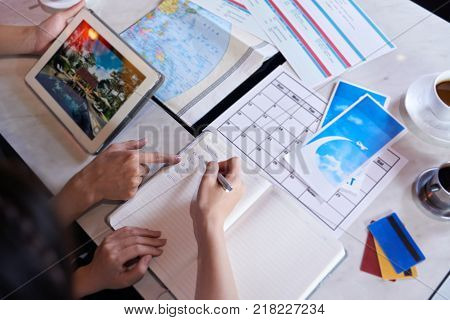 Close-up shot of unrecognizable couple taking necessary notes and planning vacation trip to Europe while sitting at table