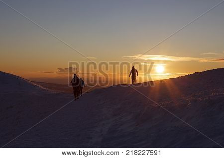 Winter sunset on Pen y Fan mountain in the Brecon Beacons National Park, UK with silhouettes of unrecognisable  climbers and a winter skies background.