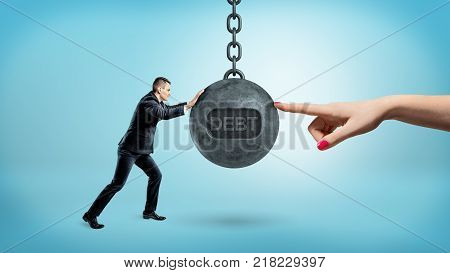 A tiny businessman pushes a large wrecking ball with a word DEBT against a giant female finger on the other side. Business and success. Financial trouble. Corporate consultant.