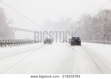 Cars driving on a highway covered with snow during a snowstorm in winter