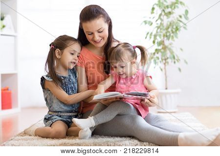 pretty mother reading book to her kids daughters