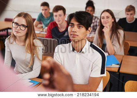 College Students In Class Viewed From Behind Teacher