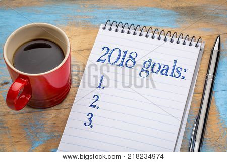 2018 goalslist in notebook a spiral notebook with a cup of coffee, goal setting and resolutions concept