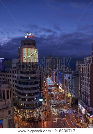 Madrid Spain - December 11 2017. Nightfall view of Gran Via street illuminated by christmas lights and neon signboards located in central Madrid. View from Callao square.