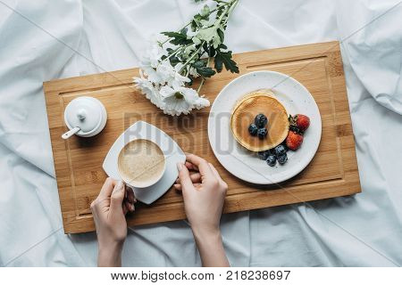 cropped shot of woman eating breakfast with pancakes and coffee in bed