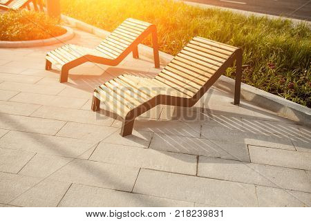 Sun loungers on the public park in the Moscow street. Bench in the town