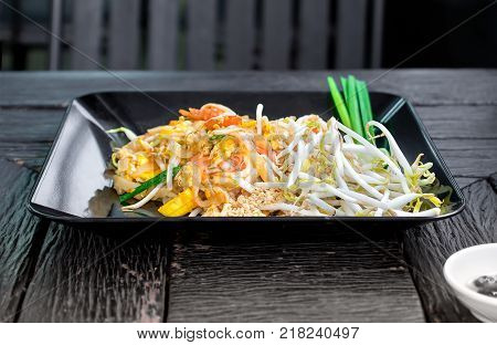 Dish of Thai styled Pan Fried Noodles Pad Thai on a wooden background