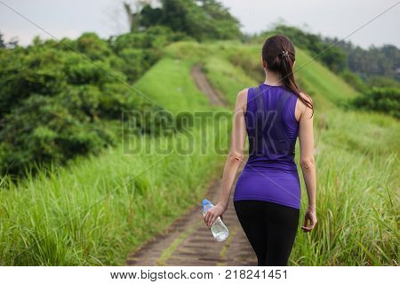 Slim girl in tight sportswear with bottle of water standing outdoors among green grass