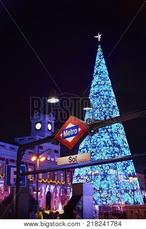 Madrid, Spain - December 12, 2017. Puerta del Sol metro station signboard at night with Real Casa de Correos illuminated by christmas lights and a shinny christmas tree in background.