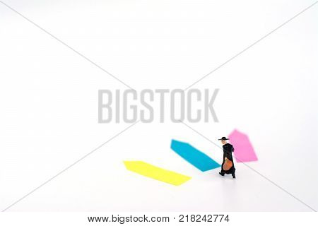 Three direction arrow choices left right or move forward miniature model figure of businessman or traveler are taking decisions for the future choice way in business concept.