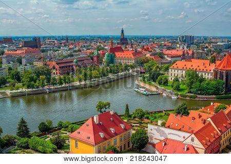 Wroclaw/Poland- August 18, 2017: aerial panoramic cityscape - river Odra, part view of Tumski Island,  historical and modern buildings, alley, park and green trees summertime, blue sky