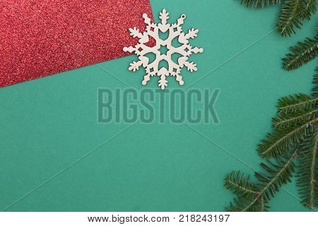 Green one-color Christmas or New Year background with red gleaming wraping paper, wooden snowflake and a natural spruce branch. Space for your text or image. Top view.