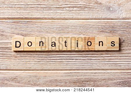 Donation word written on wood block. Donation text on table concept.