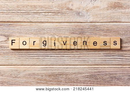 forgiveness word written on wood block. forgiveness text on table concept.