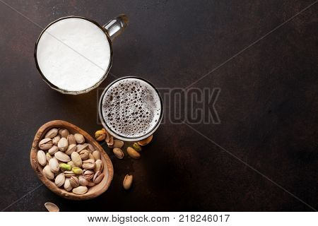 Lager beer and nuts on stone table. Top view with copy space poster