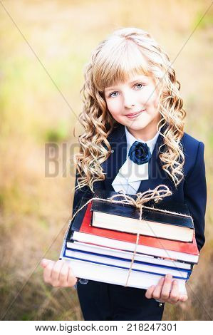 The first grader stands in the background of the autumn park. A schoolgirl with blond curls holds a stack of books in her hands, which is tied with a rope. Day of knowledge,the beginning of the school