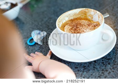 Cup of coffee and baby on background. Concept of working mother and newborn baby. Woman and mum as student.