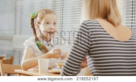 Girl with pigtail with her mum in the cafe - teen feels surprised, close up