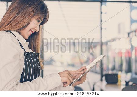 Small Business Owner Holding Tablet At Counter In Coffee Shop. Female Barista Wearing Apron Using To