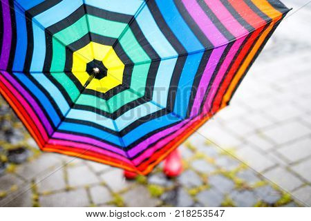 Close-up of colorful umbrella and red rain gum boots. Child on summer day. happy kid during heavy summer shower rain