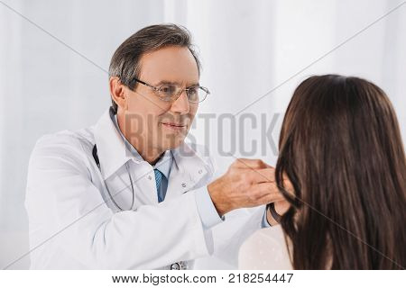male doctor palpating female patient lymph nodes