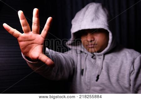 Man with Hood pushing away with his hands, repulsion with stopping hand gesture, .
