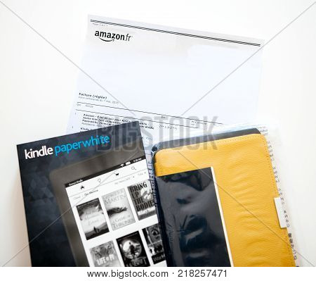 PARIS FRANCE - MAY 2016: New Amazon Kindle Paperweight e-reader electronic device and its leather cover on the white A4 invoice paper featuring the price
