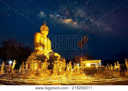 MILKY WAY, BUDDHA, AND CANDLE PROCESSION. Buddhists and worshipers start candlelight processions around pagoda with Milky Way in the sky.