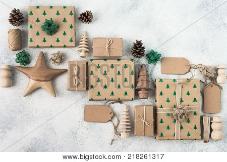 Christmas arrangement, brown present boxes with sparkling embossed fir trees, pine cones, gift tags, wooden decorations, jute twine, top view, copy space for text