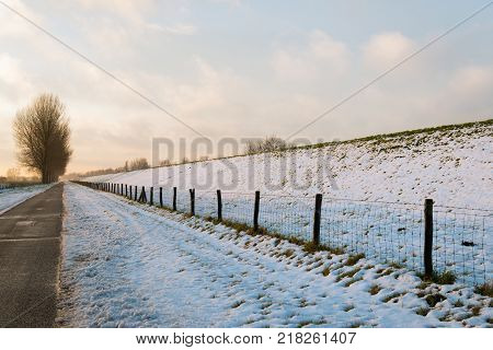Seemingly infinitely long country road along a dike in the Netherlands. At the berm of the dike is a fence with gauze and wooden poles. It is winter and almost everywhere there is snow.