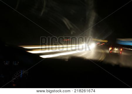 Using a long exposure to capture a night time driving experience while showcasing motion blurr on the highway and a focused interior of the drivers vehicle.