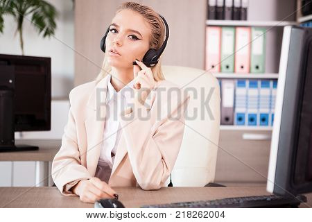 Callcenter support operator at her desk talking with clients through headset