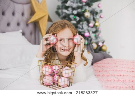 Portrait of cute cheerful little girl on Christmas morning in home interior. Child paying with holiday decorations making eye of pink balls while laying on bed. Horizontal color photo