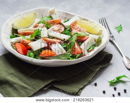 Salad with rocket, mizuna, chard, squid and tomatoes, seasoned with lemon juice and olive oil