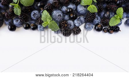 Black-blue berries on a white. Ripe blueberries blackcurrants and blackberries. Berries at border of image with copy space for text. Background berries. Top view. Various fresh summer berries on white background.