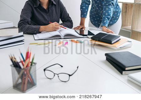 Tutor book with friends Young students campus or classmates helps friend catching up workbook and learning tutoring in classroom teaching learning People technology Education school concept.