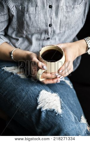 Stylish fashionable girl with a Cup of coffee and manicure in jeans.