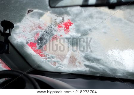 snow-covered window after a snowfall. cleaning the car window after snow
