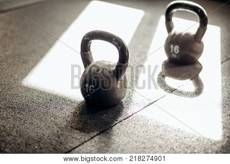 Muscular woman holding old and rusty kettle bell on to the gym floor. Focus on the kettle bell.
