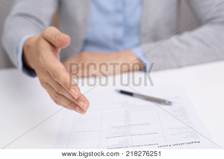 Businesswoman concluding successful deal with new company. Employer greeting job candidate and preparing application form for him. Handshake concept