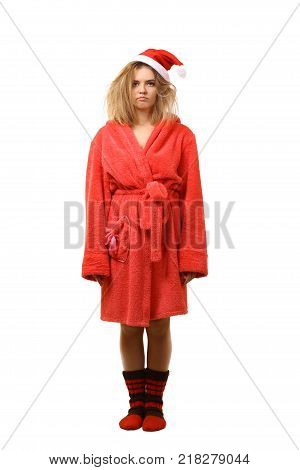 Young sleepy girl in a robe in Santa's hat. Not combed hair. Wants to sleep. New Year. Christmas. After the holiday. Have not had enough sleep. In full growth. Isolated on white background