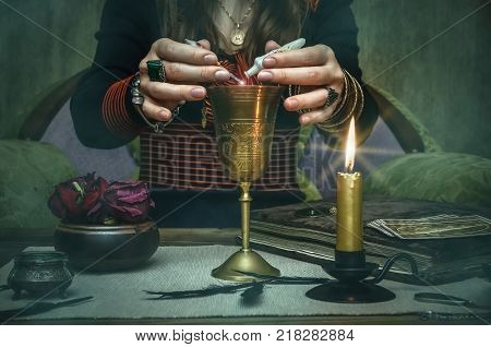Woman witch prepare a magic potion. Future reading. Tarot cards on fortune teller desk table.