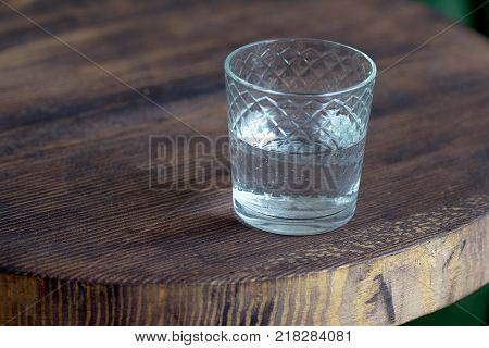 Glass Of Water As A Refreshment On A Small Wooden Table. Selective Focus Behind Blur And Bad Light.