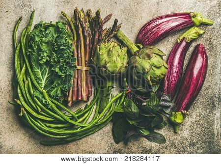 Flat-lay veriety of green and purple vegetables over grey concrete background, top view. Local seasonal produce for healthy cooking. Eggplans, beans, kale, asparagus, artichoke, basil. Clean eating