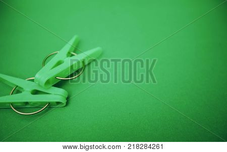 Green plastic clothes clothes pegs on a bright one-color green background. Top view. Spase for your text. Household supplies isolated. top view. Close up