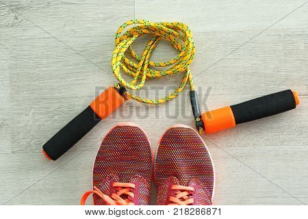 Jumping rope and sneakers on wooden background