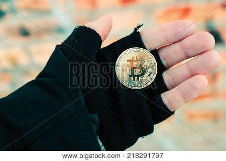 Bitcoin cryptocurrency in hand of homeless man. Man holding BTC golden coin as symbol of electronic virtual money for web banking and international network payment