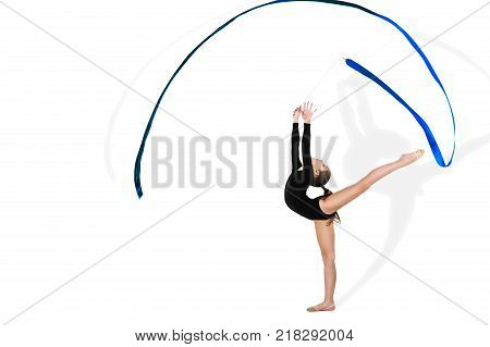 Yong gymnast in black tricot is performing exercise with blue ribbon on isolated background