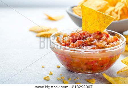 Traditional mexican homemade salsa sauce in a glass bowl and a bowl with tortilla chips on background. Party food concept.  Close-up, copy space, horizontal image